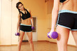 Young fit woman doing exercises with dumbells