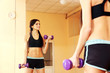 Young smiling fit woman doing exercises with dumbells