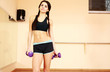 Young thoughtful fit woman doing exercises with dumbells at gym