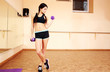 Young fit woman doing exercises with dumbells at gym