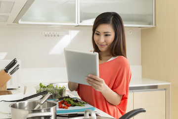 chinese woman in kitchen reading a recipe from a digital tablet.