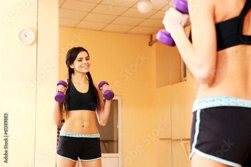 fit woman doing exercises with dumbells