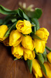 banch of Yellow tulips lying on wooden boards