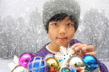 Cute Asian child in front of colorful baubles decoration