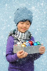 Happy Asian child holding a box of colorful Christmas baubles