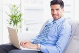 Businessman sitting on couch using his laptop smiling at camera