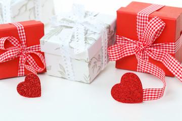 Rote und weiße Geschenke mit Schleifen und Herzen