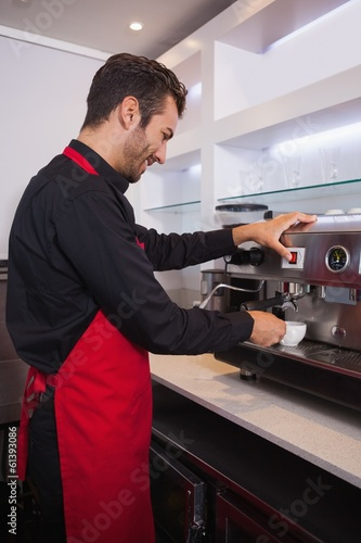 Smiling attractive barista making cup of coffee