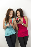 Two happy Asian women using there smartphones.