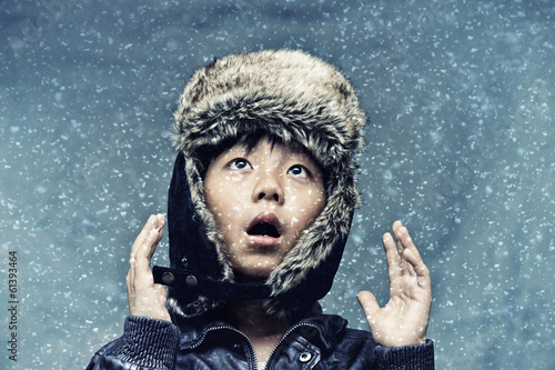 Cute boy surprised by snowfall