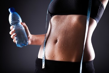 Woman after exercise with measuring tape and water bottle