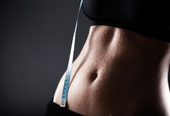Woman sporty belly after exercise with measuring tape