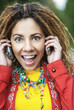 smiling woman talking on two mobile phone