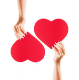 Two hands holding red hearts