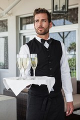 Handsome waiter holding tray of champagne