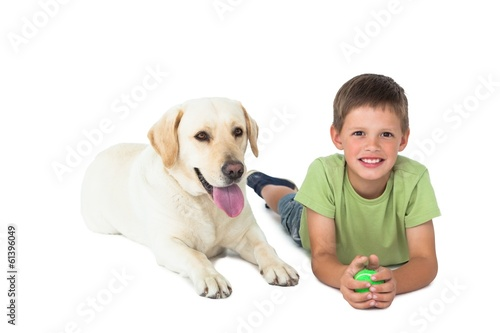 Cute little boy holding ball lying on floor with his labrador