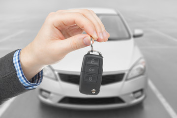Male holding car keys with remote control system