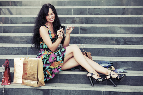 Happy young woman with shopping bags sitting on the steps