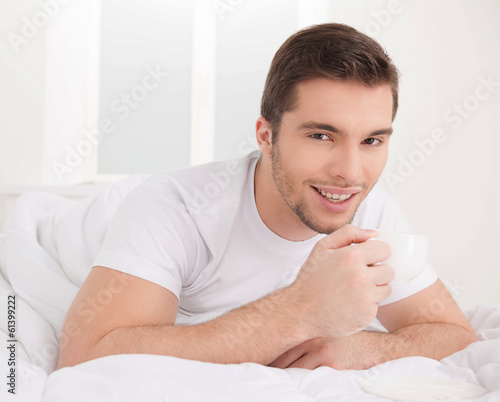 handsome male smiling laying in bed.