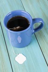 Taza de té sobre fondo de madera zul con etiqueta en blanco