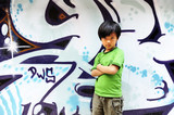 Cool Chinese boy in front of graffiti wall