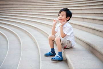 Happy schoolboy sitting on the stairs