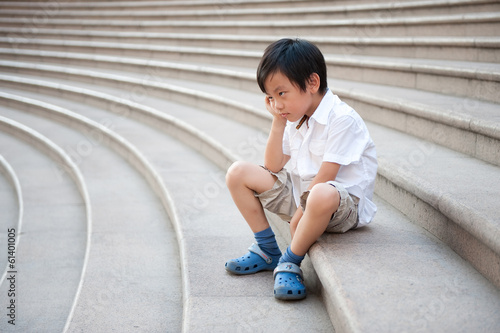 Sad boy sitting on stairs