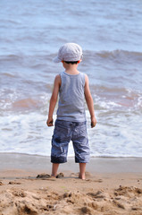 Little boy standing in front of the sea