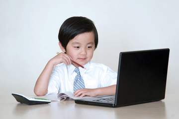 Happy Asian school boy in front of laptop computer