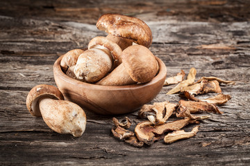 Fresh and dried organic ceps on a wooden background