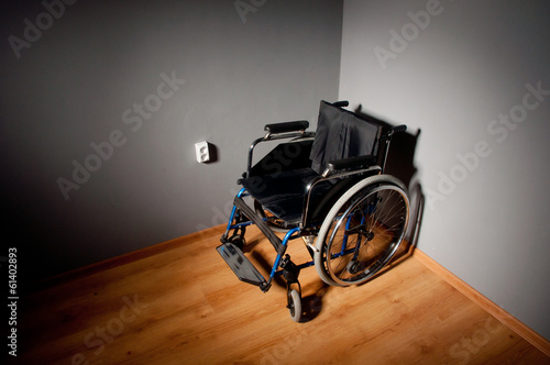 Closeup empty wheelchair on dark background and shadow in empty