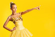 Lovely ballerina in yellow tutu pointing at something