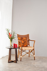 Rattan chair with orange colored pillow