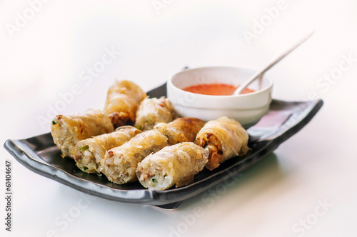 A plate of fried chinese spring rolls with chili sauce