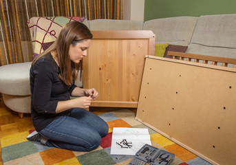Girl reading instructions to assemble furniture