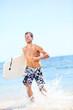 Summer beach fun surfer man running with bodyboard