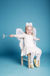 Cute little girl with butterfly costume on blue background