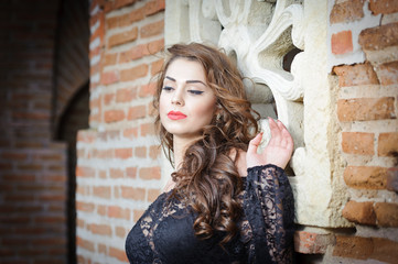 Charming young brunette woman in black lace blouse near a wall