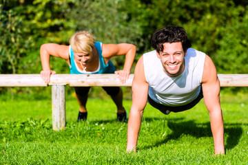 Fitness - Leute beim Training mit Liegestütze