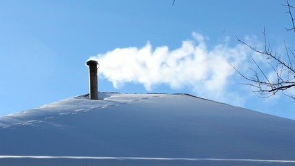 house roof with snow and white smoke from the chimney