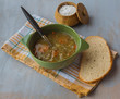 A bowl of lentil soup with a bread and salt
