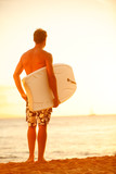 Surfer man on beach at sunset holding bodyboard