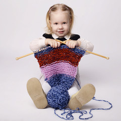 cute little girl knitting scarf