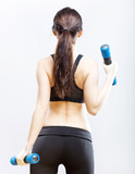 Fit woman during exercise with dumbbells, back view