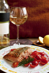 Salmon with cherry tomatoes and glass of white wine