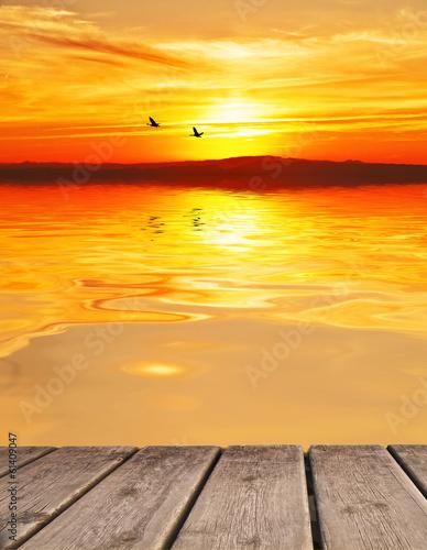 Fotobehang Een Hoekje om te Dromen puesta de sol en un mar en calma