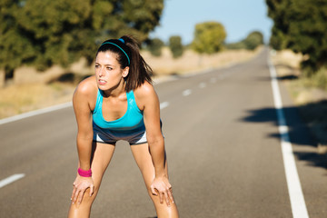 Tired woman sweating after running on road