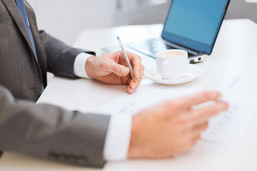 man hands with contract and pen, coffee and laptop