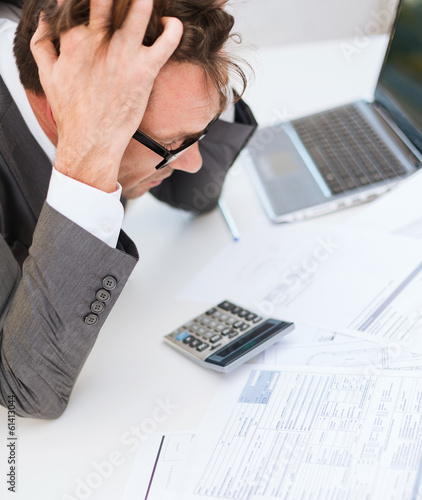 businessman with papres, laptop and calculator