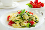 Pasta tagliatelle with zucchini and tomatoes.